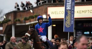 Jockey Paddy Brennan celebrates winning the King George VI Steeple Chase on Cue Card during day one of the William Hill Winter Festival at Kempton Park Racecourse. Photograph: Andrew Matthews/PA