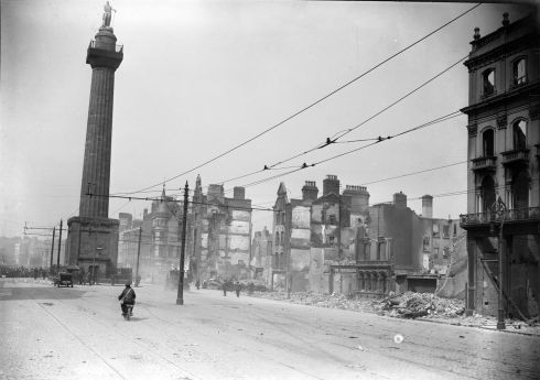 Crowds gathering to the rear of Nelson's Pillar are kept away from the crumbling ruins of Sackville Street.