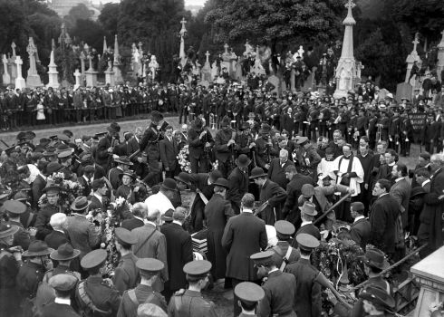Members of the Irish Citizen Army and the Volunteers, clergy, and mourners look on as the body of O'Donovan Rossa is lowered into his grave.