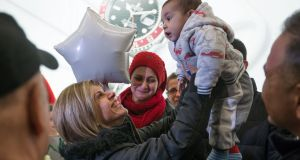 Tima Kurdi lifts up her 5-month-old nephew Sherwan Kurdi after her brother Mohamed Kurdi and his family arrived in Vancouver. Photograph: Darryl Dyck/The Canadian Press via AP