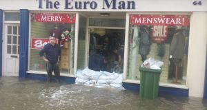 Staff bail out a flooded shop in Midleton, Co Cork on Wednesday after flooding caused by Storm Frank. Photograph: Barry Roche/The Irish Times