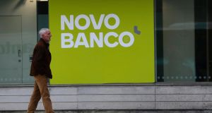 A man walks past an office of the Portuguese bank Novo Bank (New Bank) in Lisbon.