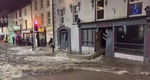 Water flows through buildings and down the street in Graignamanagh, Co Kilkenny on Tuesday night. Photograph: Paul B via Twitter