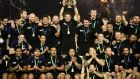 New Zealand's flanker and captain Richie McCaw holds the Webb Ellis Cup aloft as he celebrates with teammates. Photograph: AFP/Getty Images