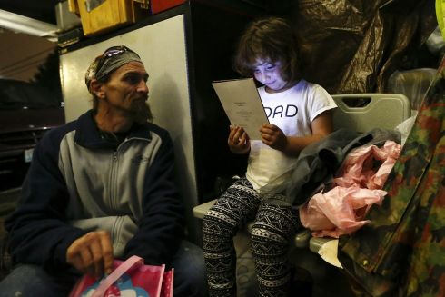 Emma Savage, 6, opens a birthday card given to her by her dad Robert Rowe, 42, a day labourer who had just returned from a 12-hour working day to SHARE/WHEEL Tent City 3 outside Seattle, Washington.  Photograph: Shannon Stapleton /Reuters