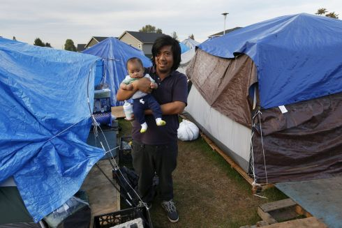 David Yu, 32, poses with his three and a half month old son Joseph, outside his tent at SHARE/WHEEL Tent City 3 outside Seattle, Washington.  Photograph: Shannon Stapleton /Reuters