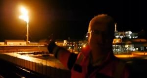 Shell E&P Ireland's John Egan in a still from a Youtube video from New Year's Eve, discussing the flaring of gas at the Corrib plant, seen in the background. Photograph: Shell/Youtube