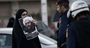 A Bahraini woman holds a picture of Shia cleric Nimr al-Nimr   during  a protest after his execution  by Saudi authorities. Photograph: Mohammed Al-Shaikh/AFP/Getty Images