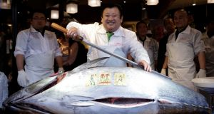 Kiyoshi Kimura, president of sushi restaurant chain   Kiyomura Co,  with the 200kg bluefin which sold for ¥14 million: The popularity of Japanese food means bluefin has become more sought after by diners in other countries, notably China. Photograph:   Kiyoshi Ota/EPA