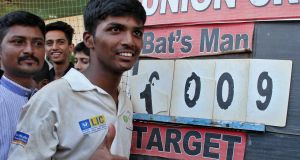 Pranav Dhanawade, 15, poses in front of the scoreboard after scoring 1,009 not out in an inter-school cricket tournament in Mumbai, a new record score in a cricket match. Photograph: Reuters