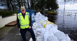 Noel Fallon keeps guard at  sandbanks between his house and the swollen River Shannon at Wolfe Tone Terrace in Athlone. Photograph: Bryan O'Brien/The Irish Times