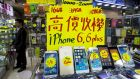 A sign shows the prices of the Apple iPhone 6 and 6 Plus at a store in Hong Kong