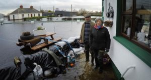 Mikey and Gertie Dunning at the rear of their farmhouse in Golden Island outside Athlone. Their home is entirely surrounded by water and they are on 24-hour watch to monitor sandbags and electric pumps. Photograph: Bryan O'Brien