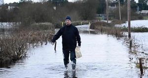 Padraig Keenan walks through floods near his home in Golden Island, Athlone. Photograph: Bryan O'Brien/The Irish Times