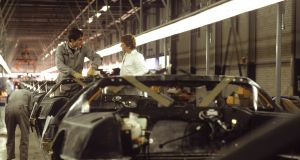 Two workers on the assembly line at the DeLorean Motors factory talk while a third checks a wheel base in November 1981. File photograph: Bill Pierce/Life/Getty