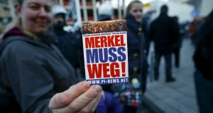 "A supporter of the anti-immigration right-wing movement PEGIDA (Patriotic Europeans Against the Islamisation of the West) holds up a sticker for a photo during a demonstration rally in Cologne, Germany on Saturday. The sticker reads ""Merkel must go!"". Photograph: Wolfgang Rattay/Reuters"