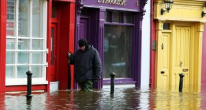 A man walks past shop fronts as flooding continues in Bandon, Co Cork, following storm Frank in December 2015. Photograph: PA