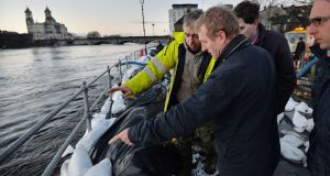 Taoiseach Enda Kenny examines flood defences on the banks of the east side of the river Shannon in Athlone in December. Photograph: Alan Betson/The Irish Times