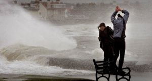 Two girls stand on a bench as they brave waves at Troon promenade in Scotland Photograph: Reuters