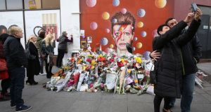People take a selfie by floral tributes in front of James Cochran's mural of David Bowie in Brixton, south London,  two days after the announcement of Bowie's death. Photograph: Justin Tallis/AFP/Getty Images