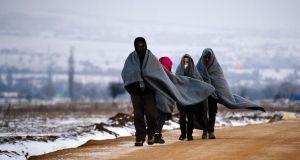 Refugees use their sleeping blankets to keep warm as they walk along snow-covered fields near the Macedonian-Serbian border. Photograph: Dimitar Dilkoff/AFP/Getty Images