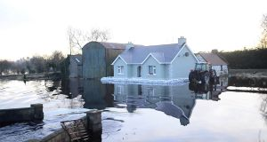 Floods surround a house in the Golden Island area of Athlone. Fianna Fáil claim the budget for flood relief works in 2016 had been cut by 14 per cent.  Photograph: Bryan O'Brien/The Irish Times