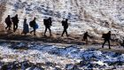 Migrants and refugees walk along snow-covered fields after crossing the Macedonian border into Serbia, near the village of Miratovac, on Tuesday. Temperatures in Syria are forecast to drop to -20 degrees this week. Photograph: Dimitar Dilkoff/AFP/Getty Images