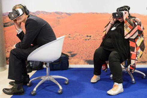VIRTUAL ECONOMY: Artist Lynette Wallworth and an unidentified  participant try out virtual reality glasses at the World Economic Forum in Davos, Switzerland. Photograph: Laurent Gillieron/EPA