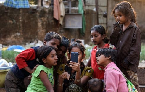 CHILD POVERTY: Homeless children watch a movie on a mobile phone in Mumbai, India. Photograph: Divyakant Solanki/EPA