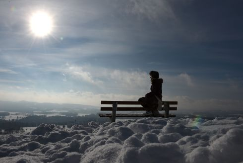 WINTER SUN: A young girl sits on a bench near Irschenberg, southern Germany. Photograph: Christof Stache/AFP/Getty Images