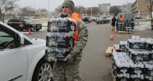 Michigan National Guard member Zach Burrell helps distribute water to residents in their cars in Flint, Michigan.  Photograph: Rebecca Cook/Reuters