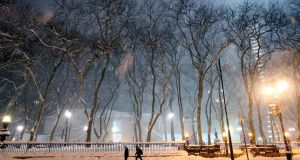 Pedestrians walk through the snowy streets in New York. Photograph:   Yana Paskova/Getty Images