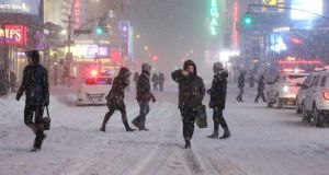 Pedestrians walk through the snowy streets near Times Square as all cars but emergency vehicles are banned from driving on the road on Saturday in New York City. Photograph: Yana Paskova/Getty Images