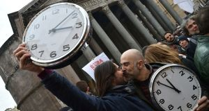 "Supporters of same-sex civil union kiss holding alarm clocks ""to wake up Italy"" on Saturday near the Pantheon in central Rome. An estimated one million people took to the streets of Italy, to signal their support for civil union legislation. Photograph: Alberto Pizzoli/AFP/Getty Images"