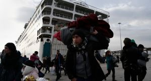 Refugees and migrants walk after disembarking from the ferry 'Eletherios Venizelos' at the port of Piraeus, near Athens, Greece. The ship was carrying about 2,500 refugees and migrants that had landed on the Greek island of Myilene, coming from Turkey. Greece is under pressure from EU colleagues to control the flow of migrants into the union. Photograph: Yannis Kolesidis/EPA.