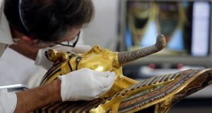 German restorer Christian Eckmann carrying out restoration work on the golden mask of King Tutankhamun  after the beard was accidentally broken off and hastily glued back, at the Egyptian Museum in Cairo. Photoghraph: Amr Nabil/AP