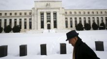 A man walks past the snow-covered grounds of the US Federal Reserve in Washington DC Photograph: Reuters