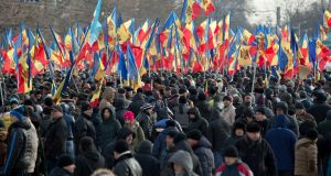 People hold flags during a large protest in Chisinau, Moldova, last Sunday. More than 15,000 people gathered to protest against the government, demanding early elections. Photograph: AP Photo/Vadim Ghirda