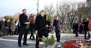 Turkish president Recep Tayyip Erdogan  places carnations as he visits the site of the suicide bomb attack that killed 10 German tourists in central Istanbul. Photograph: Murat Cetinmuhurdar/Reuters