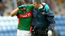 Mayo's Lee Keegan is helped from the field by Dr Seán Moffatt after suffering a clash of heads with Cork's Eoin Cadogan in Páirc Uí Rinn. Photograph: James Crombie/Inpho