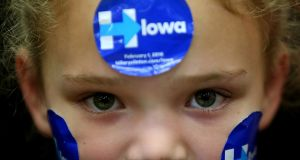 A young supporter wears campaign stickers on her face as Democratic presidential candidate  Hillary Clinton speaks during a 'get out to caucus' event at Washington High School on January 30th in Cedar Rapids, Iowa. Photograph: Justin Sullivan/Getty Images