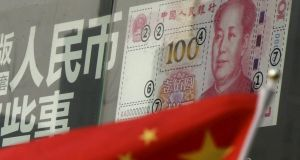 A Chinese national flag is seen in front of a poster explaining the design of the new 100 yuan banknote