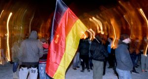 Pegida demonstrators walk with a German flag during a demonstration in Potsdam last month. Anti-racism campaigners and migrant support groups are to hold a rally in Dublin on Saturday to protest against the establishment of an Irish branch of the anti-Islamic group Pegida. Photograph: Ralf Hirschberger/EPA.