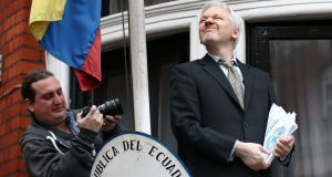 Wikileaks founder Julian Assange squints in the sunlight as he prepares to speak from the balcony of the Ecuadorian embassy. Photograph: Carl Court/Getty Images
