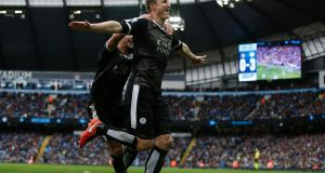 Leicester City's Robert Huth (R) celebrates scoring his team's third goal at the Etihad Stadium Photograph: / AFP / Adrian Dennis