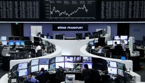 Traders work at their desks in front of the German share price index, at the stock exchange in Frankfurt, Germany. Europena share have fallen by 3 per cent.