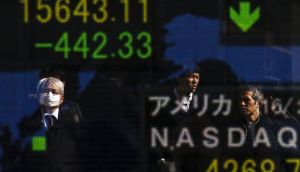 People are reflected in a display showing market indices outside a brokerage