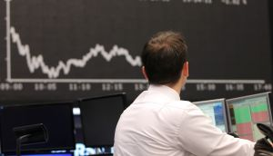 A trader looks up at the board displaying the  course of the DAX stock market index  in Frankfurt