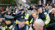 Taoiseach Enda Kenny is escorted by gardaí  as he passes a small group of protesters at the turning of the sod on the  Cork Event Centre in  Cork city. Photograph:  Daragh Mc Sweeney/Provision