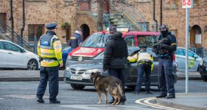 Armed gardaí and sniffer dogs at a checkpoint at the corner of Bridgefoot Street and Oliver Bond Street in the South Inner City ahead of the funeral of David Byrne in St Nicolas of Myra, Francis Street, Dublin 8 on Monday.